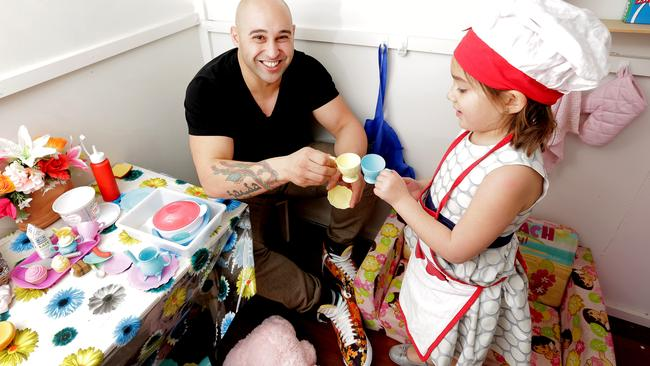 Shane shares a cup of tea with his daughter Jayda, inside her cubby house. Picture: Nicole Cleary