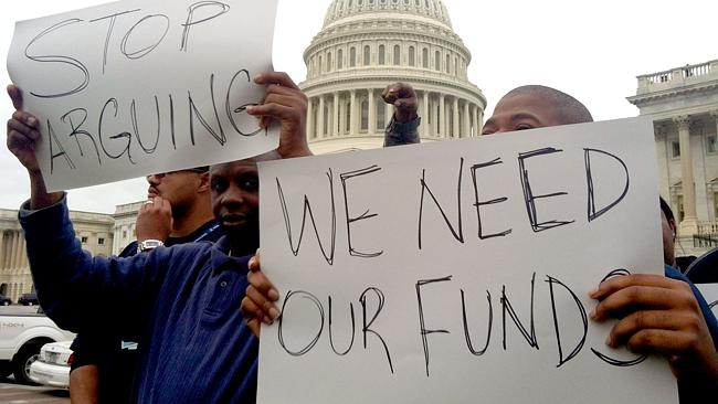 Protesters hold placards urging the US Congress to end the federal government shutdown Picture: AFP, Michael Mathes.