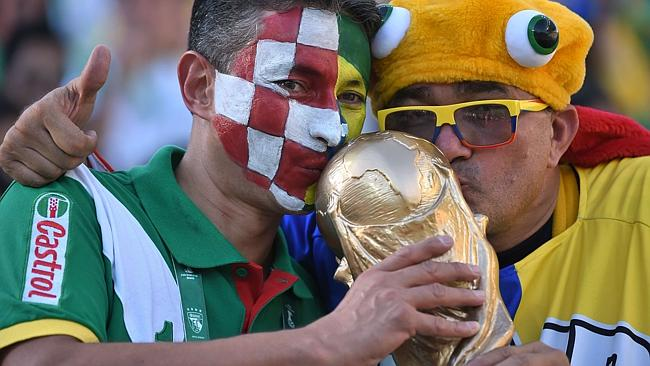 Brazilian fans kiss a replica of the World Cup trophy prior to a Group A football match between Brazil and Croatia. Picture: AFP