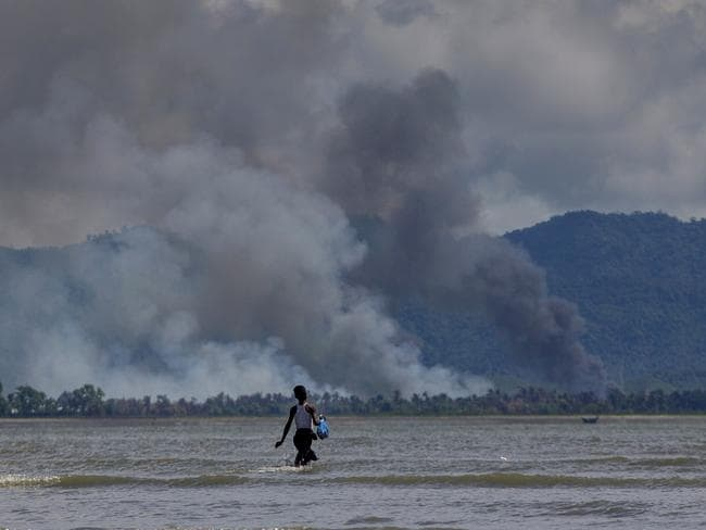 A Bangladeshi boy walks towards a parked boat as smoke rises from across the border in Myanmar. Picture: Dar Yasin/AP