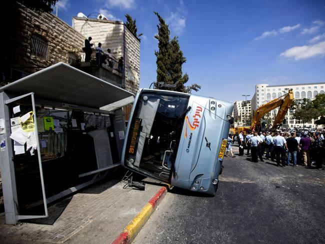 One dead ... A damaged bus flipped over after attack in Jerusalem. Picture: AP
