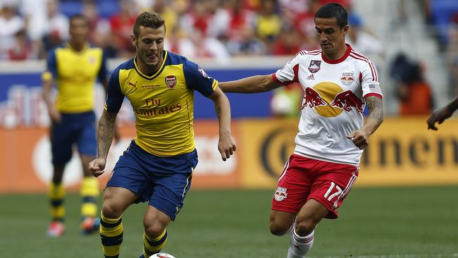 Jack Wilshere of Arsenal fights for the ball with Aussie Tim Cahill of New York Red Bulls.