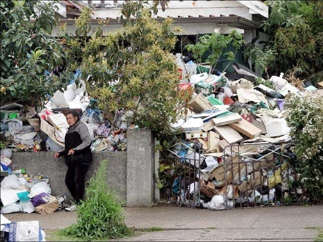 The rubbish reached such a height that the gate and fence could no longer contain it with some spilling onto the footpath.