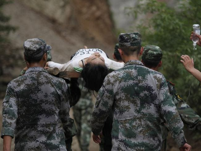 Survivor ... rescuers carry an injuried resident after an earthquake in China's mountainous Yunnan province.