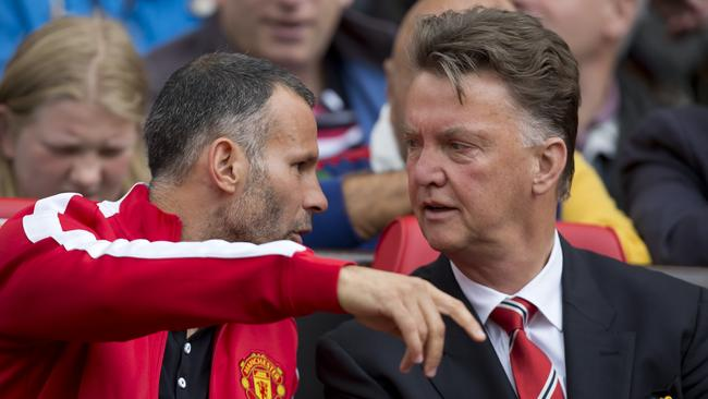 Manchester United's manager Louis van Gaal chats with his assistant Ryan Giggs.