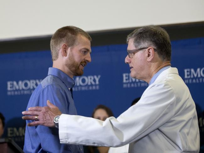 Amazing recovery....American Ebola victim Dr. Kent Brantly, left, embraces Dr. Bruce Ribner, medical director of Emory's Infectious Disease Unit, after being released from Emory University Hospital after recovering with the help of ZMapp. Picture: AFP