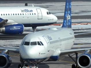 A JetBlue Airbus A320, that just landed, taxis past another JetBlue plane being towed to a gate at John F Kennedy (JFK) International Airport, in New York, 18/02/2007 file photo. The main runway at New York's JFK International will be closed for four months starting 01/03/2010.