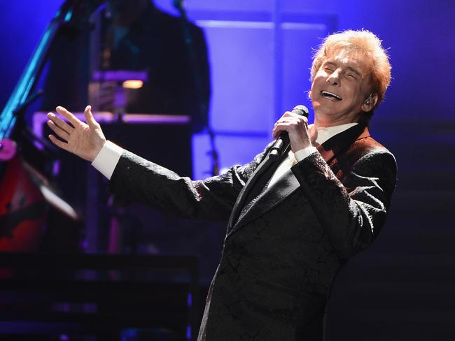 "In recovery ... Barry Manilow in action. The 72-year-old singer, who had just played a sold-out show in Memphis, was taken to a Los Angeles hospital ""due to complications from emergency oral surgery"". Picture: AFP/Getty Images North America/Stephen Lovekin"