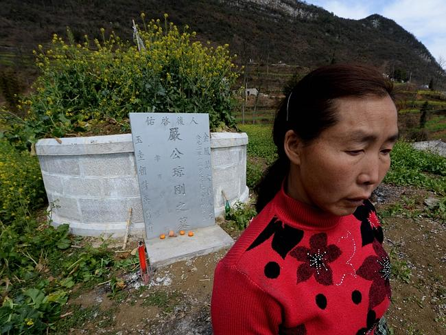 Grief...Zhang Yan visits her husband's grave in her village near Anshun, Guizhou Province. Her husband was killed in the mines, after their teenage son begged him to find another job. Picture: AFP