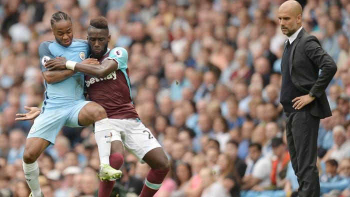 TOPSHOT - West Ham United's French defender Arthur Masuaku vies with Manchester City's English midfielder Raheem Sterling (L) as Manchester City's Spanish manager Pep Guardiola (R) looks on during the English Premier League football match between Manchester City and West Ham United at the Etihad Stadium in Manchester, north west England, on August 28, 2016. / AFP PHOTO / OLI SCARFF / RESTRICTED TO EDITORIAL USE. No use with unauthorized audio, video, data, fixture lists, club/league logos or 'live' services. Online in-match use limited to 75 images, no video emulation. No use in betting, games or single club/league/player publications. /