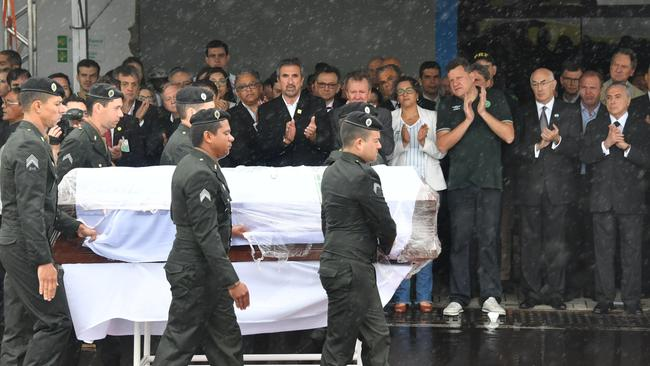 Brazilian President Michel Temer (far right) applauds as one of the coffins passes by. Picture: AFP/Nelson Almeida