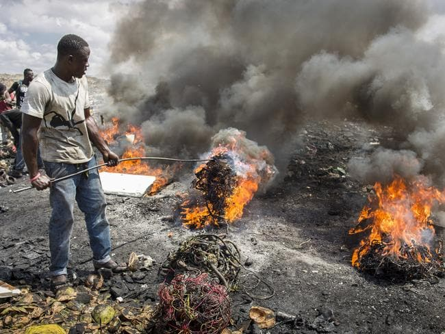 Young African men burn electronic waste on the world's biggest electronic scrap yard in Agbogbloshie, in the Ghanaian capital of Accra. Picture: Thomas Imo.