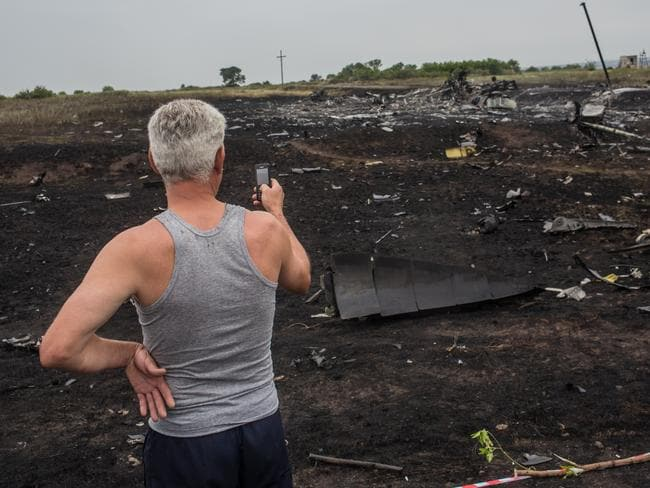 An onlooker uses his phone to photograph the scene of the Air Malaysia plane crash. Picture: Brendan Hoffman