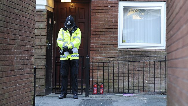 A Police officer stands outside the front door of a house in Manchester, England, where the body of a 14-year old girl was found after being mauled by dogs.