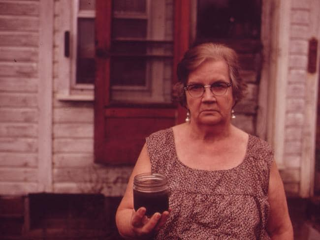 Mary workman holds a jar of undrinkable water that comes from her well, and filed a damage suit against the Hanna coal company. She had to transport water from a well many kilometres away. Although the coal company owns all the land around her, and many roads are closed, she refused to sell at the time the photo was taken. 1973. Picture: Erik Calonius/Documerica/US National Archives