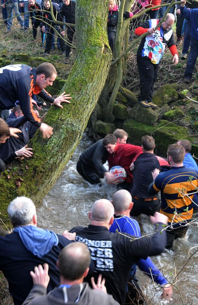 Players compete for the ball during the Royal Shrovetide Football match in Ashbourne.