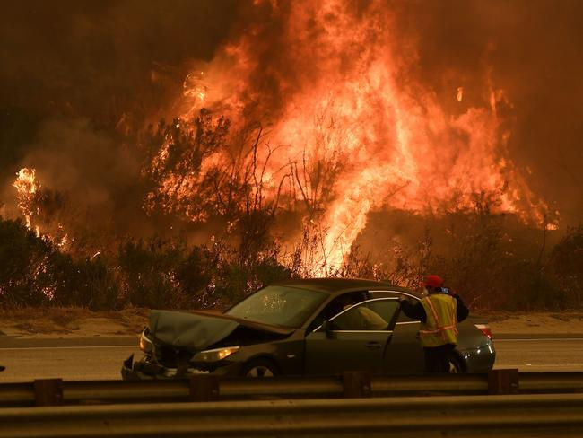 A woman involved in a traffic accident waits to get towed beside a wall of flames on the 101 highway. Picture: AFP/Mark Ralston