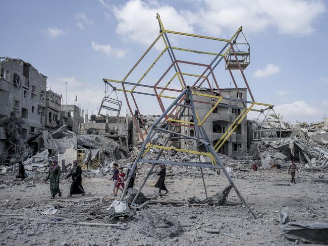 Life goes on ... Palestinians make their way past rubble and a mini ferris wheel during the ceasefire.