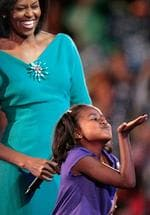 <p>Michelle Obama (L), wife of presumptive Democratic nominee U.S. Sen. Barack Obama (D-IL), watches her daughters Sasha blow a kiss to her father to Barack Obama who appeared on a video screen during day one of the Democratic National Convention (DNC) at the Pepsi Center August 25, 2008 in Denver, Colorado. The DNC, where U.S. Sen. Barack Obama (D-IL) will be officially nominated as the Democratic candidate for U.S. president, starts today and finishes August 28th.</p>