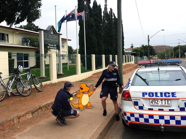 Supplied image obtained Thursday, July 14, 2016 of Police in Mount Isa escorting a Charmander from a local school after Pokemon Go users trespassed onto the property. (AAP Image/Queensland Police) NO ARCHIVING, EDITORIAL USE ONLY