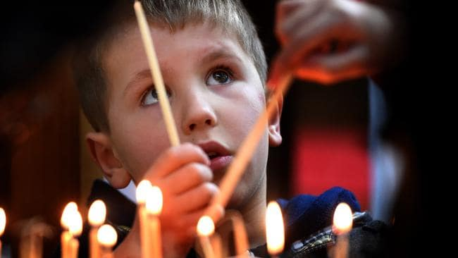 Jake, 5, lights a candle during the memorial service at North Melbourne's Ukranian Catholic Church. Picture: Tony Gough
