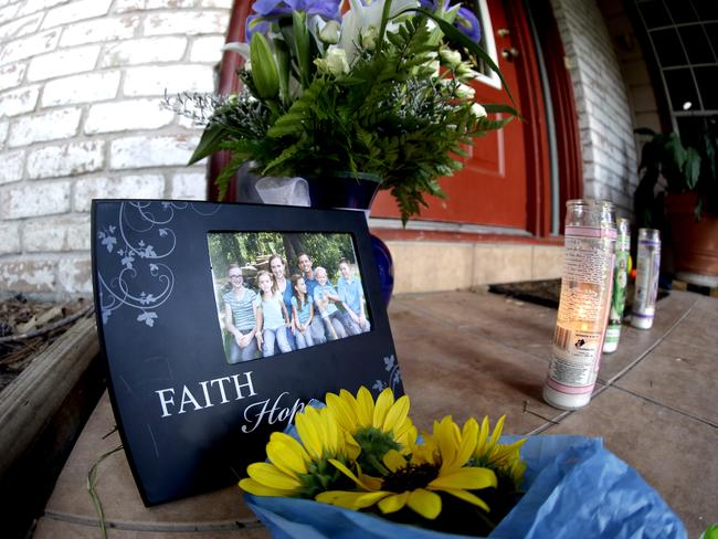 Tragic ... a photograph, flowers and candles are left on the porch where the fatal home shooting took place.