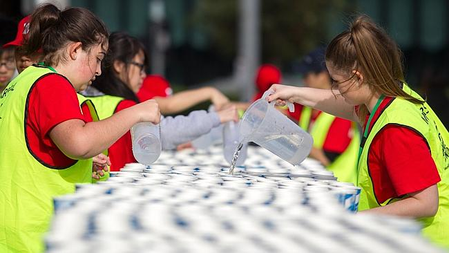 Drinks are prepared before runners reach the drink station in Queensbridge Square, South Bank. Picture: Sarah Matray