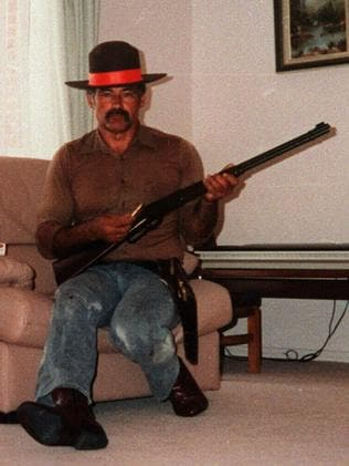 Ivan Milat, wearing a sheriff's badge, poses in his lounge room with firearms.