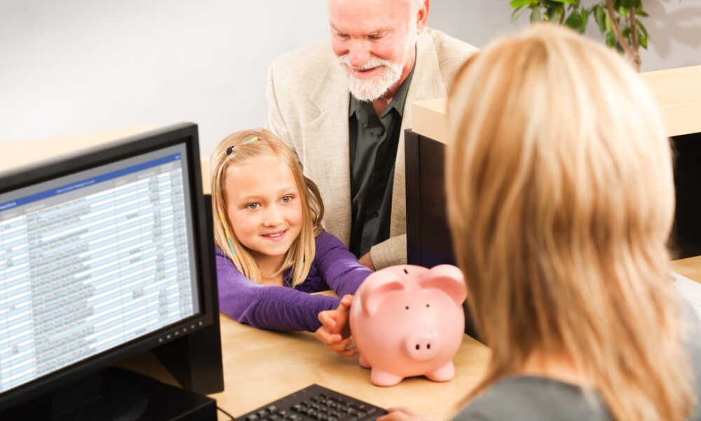 A cheerful grandparent helping a smiling young girl grandchild with her piggy bank savings. Opening a children bank account with the bank teller in a retail bank counter. Photographed indoors in horizontal format.