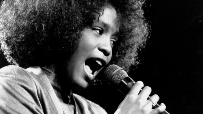 Whitney Houston belts out a song during a benefit concert at Boston Garden in 1986.