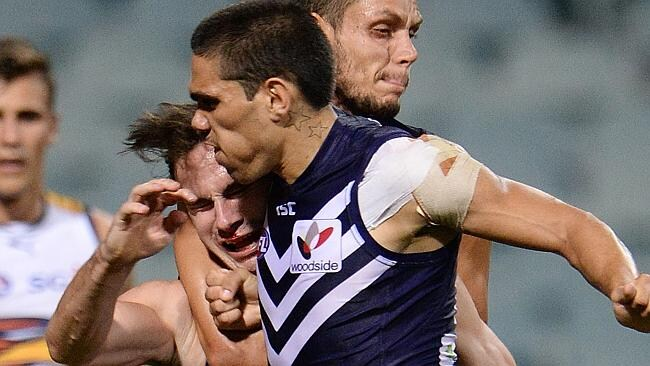 West coast Eagles' Brant Colledge is tackled by Fremantle's Michael Walters. Photo by Daniel Wilkins.