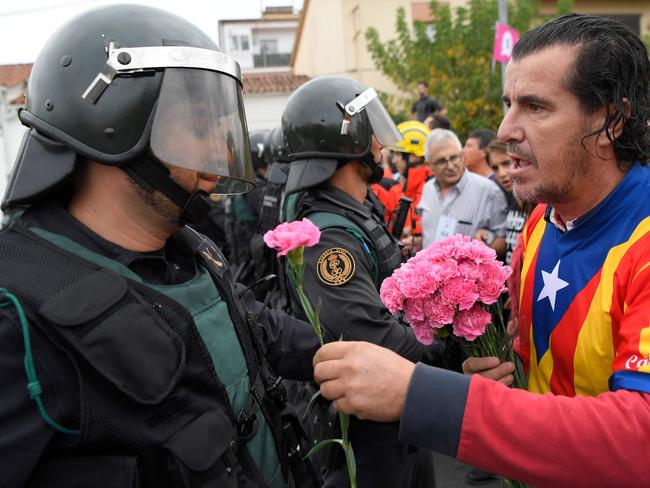 A man gives a carnation to a Spanish Civil Guard office in Sant Julia de Ramis. Picture: AFP/Lluis Gene