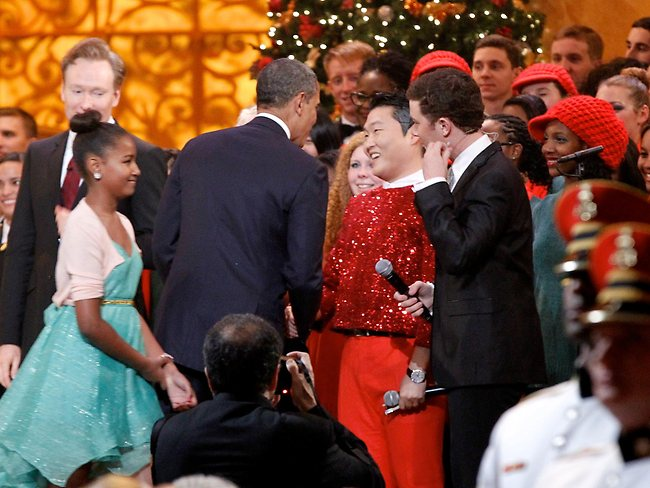 "U.S. President Barack Obama shakes hands with South Korean musician PSY, next to host Conan O'Brien (L) and performer Scotty McCreery (R) during the ""Christmas in Washington"" concert at the National Building Museum in Washington, D.C. (Molly Riley-Pool/Getty Images)"