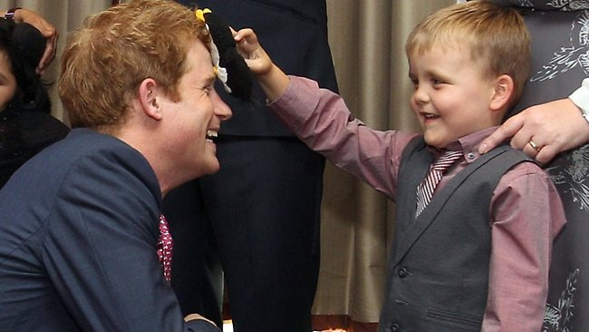 Britain's Prince Harry talks to Alex Logan who puts a toy penguin against his head.
