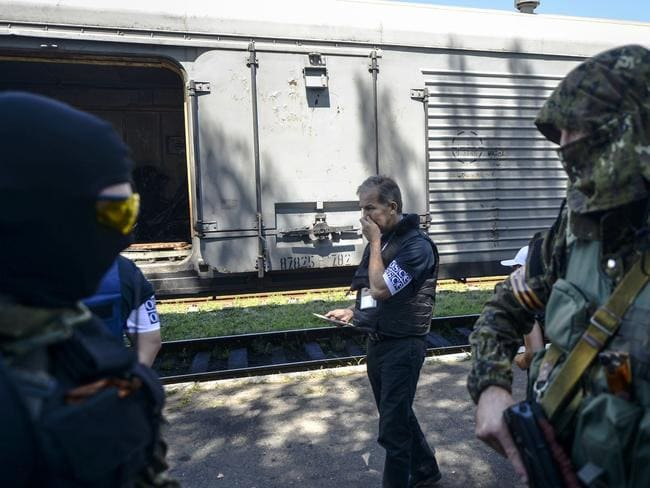 'Satisfactory' handling ... a monitor from the Organisation for Security and Cooperation in Europe (OSCE) and members of a forensic team cover their noses at the railway station in Torez. Picture: Bulent Kilic