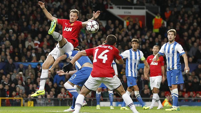 Manchester United's Jonny Evans, left, jumps for a ball during the Champions League group A soccer match between Manchester United and Real Sociedad.