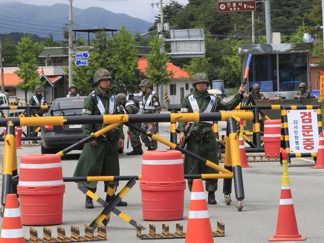 On guard...South Korean army soldiers stand at a checkpoint as they search for an armed South Korean soldier who fled after killing five of his comrades and wounding seven at an outpost near the North Korean border. Picture: AP