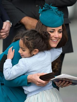 Catherine, the Duchess of Cambridge receives a hug from a little girl during a Maori welcome at Dunedin airport. Picture: AFP