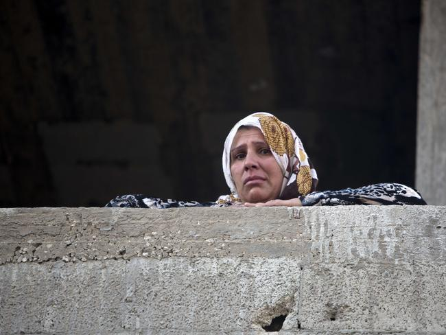 Nowhere to hide ... A Palestinian woman looks from a balcony at the wreckage left by an Israeli air strike, killing three people and wounding four others in Gaza City.