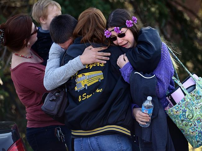 Shock ... Parents and students embrace along School Road near Franklin Regional High School after 21 students were stabbed. Picture: AFP