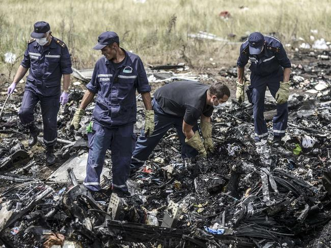 Grim scene ... Ukrainian State Emergency Service employees search for bodies among the wreckage at the crash site of Malaysia Airlines Flight MH17. Picture: Bulent Kilic