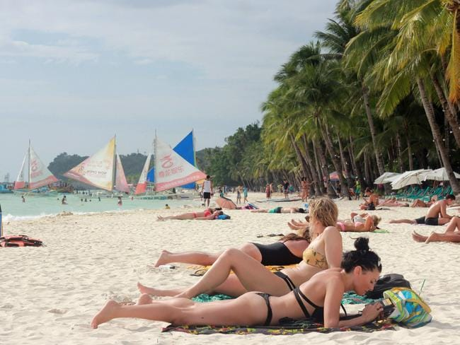 Tourists relax along a beach in Boracay island in Malay town, Aklan province, central Philippines on April 7, 2018. The Philippine tourism industry scrambled on April 6 to manage the fallout from the temporary shutdown of its world-famous Boracay island, which threw into chaos trips planned by hundreds of thousands of tourists. / AFP PHOTO / -