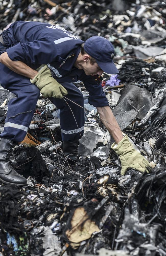 Sifting the rubble ... Ukrainian State Emergency Service employees search for bodies among the wreckage at the crash site of Malaysia Airlines Flight MH17, near the village of Grabove, in the region of Donetsk, Ukraine.