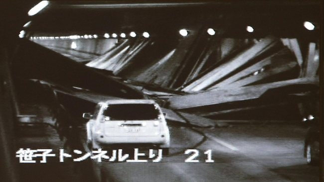 This screen grab taken from video from highway operator Central Nippon Expressway Company Limited shows a passenger vehicle (left) stopping in front of the collapsed roof inside the highway tunnel on Sunday. Picture: AFP/JIJI PRESS/Central Nippon Expressway Company Limited