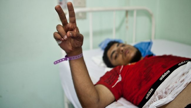 A wounded supporter of Egypt's ousted President Mohammed Morsi lies on the bed at a hospital after shooting happened at the Republican Guard building in Nasser City, Cairo, Monday, July 8, 2013. Egyptian soldiers and police opened fire on supporters of the ousted president early Monday in violence outside the military building in Cairo where demonstrators had been holding a sit-in, government officials and witnesses said. (AP Photo/Virginie Nguyen Hoang)