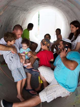 Duck and cover ... Israelis hide in a large concrete pipe used as a shelter during a Palestinian rocket attack on the southern Israeli village of Nitzan.