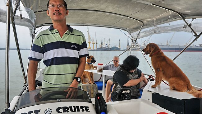 Joe Howe, owner of Pet Cruise, taking customers on a boat tour in Singapore.