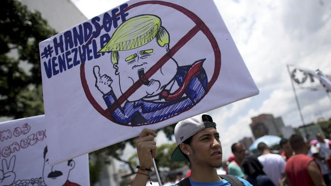 A government supporter holds a placard against Trump on September 19. Picture: Ariana Cubillos