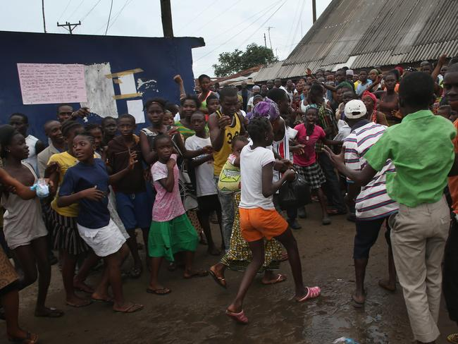 On the run ... a family flees an Ebola isolation centre in Monrovia, Liberia, after a mob forced open the gates. Picture: Getty