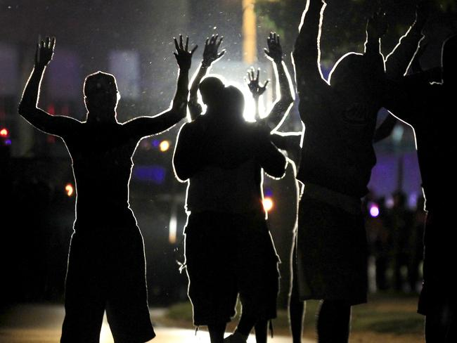 No surrender ... With their hands raised, residents gather at a police line as a neighbourhood is locked down following skirmishes in Ferguson, Missouri. Source: AFP